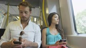 pessoas : Travelers using smartphones and 4g or wireless internet network sms texting or working while commuting to work in train. Multiracial Asian woman and Caucasian man on smart phone on commute to work. Vídeos