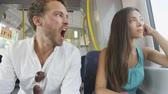 işadamı : Yawning tired man commuting in train transport. Commuters tired in transportation. Young people on commute  multiracial Asian woman and Caucasian man going to work being bored. Stok Video