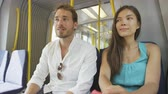 trilho : Train passengers. Commuters sitting in transport smiling happy in public transportation system commuting to work or other travel. Couple  multiracial Asian woman and young Caucasian man.