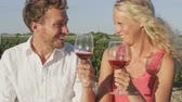 uva : Wine drinking couple at vineyard laughing toasting having fun. Romantic woman and man drinking red or rose wine smiling happy doing toast. Lovers outside enjoying wine. Young Caucasian man and woman.