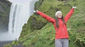 cheerful : Enjoyment woman by waterfall Skogafoss happy on Iceland posing serene and free outdoors. Girl traveler visiting famous tourist attractions and landmarks in Icelandic nature landscape on the ring road. Stock Footage