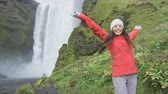 pessoas : Blissful woman by waterfall Skogafoss joyful and happy turning and spinning dancing in bliss and joy on Iceland. Girl visiting tourist attraction and landmark in Icelandic nature on the ring road. Vídeos