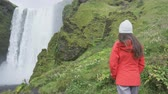 brasão : Waterfall - Tourist woman by Skogafoss on Iceland looking at waterfall. Girl visiting famous tourist attractions and landmarks in Icelandic nature landscape on the ring road. RED EPIC SLOW MOTION