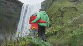 cheerful : Iceland tourists people walking by waterfall Skogafoss. Romantic couple visiting famous tourist attractions and landmarks in Icelandic nature landscape on the ring road. RED EPIC SLOW MOTION. Stock Footage