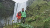 wodospad : Hiking travel couple by waterfall on Iceland outdoors  Skogafoss. People visiting famous tourist attractions and landmarks in Icelandic nature landscape on the ring road. RED EPIC SLOW MOTION. Wideo