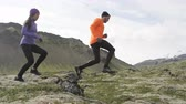 jumping : Sport running. Runners on cross country trail jumping outdoors working out. Fit young fitness model man and asian woman training outside in mountain nature on Snaefellsnes  Iceland. RED EPIC  120 FPS.