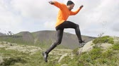 движение : Sport running man in cross country trail run. Fit male runner exercise training and jumping outdoors in mountain nature with Snaefellsjokull  Snaefellsnes  Iceland. RED EPIC  120 FPS SLOW MOTION. Стоковые видеозаписи