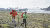 seyahat : Hiking adventure travel people walking towards camera on Iceland living active healthy lifestyle wearing backpacks by glacier and glacial lagoon  lake of Fjallsarlon  Vatnajokull. RED EPIC  REAL TIME