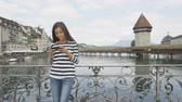 pomost : Woman using smart phone app in Lucerne Switzerland. Travel tourist with smartphone by landmark Kapellbrücke Chapel Bridge and Wasserturm water tower  Reuss River. RED EPIC footage