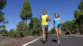 caminhada : Running couple exercising living healthy lifestyle talking starting jogging on mountain forest road. Sport runners on run outdoors working out. Fit young fitness model man and asian woman outside