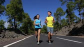 floresta : Running runner man and woman jogging training on mountain road.  Fitness runners working out for marathon on forest road in amazing nature landscape. Two models exercising.