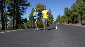 amarelo : Runners running - runner man and woman jogging training on mountain road.  Fitness couple working out for marathon on forest road in amazing nature landscape. Two models exercising. Stock Footage