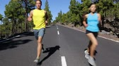 Sport fitness running people jogging outdoors on mountain road. Male and female fitness model working out training for marathon run in nature landscape. Two young runners exercising outside.
