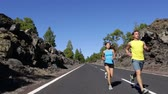 mulheres : Running fitness sport people. Runner man and woman couple jogging training on mountain road. Athletes runners working out for marathon on forest road in amazing nature landscape. Two models exercising