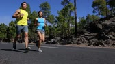 floresta : Healthy running runner man and woman workout on mountain road. Jogging male and female fitness model working out training for marathon on forest road in amazing nature landscape. Runners exercising Vídeos