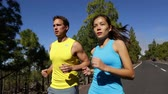 casal : Exercise running sport. Runners training on road for marathon run outdoors working out. Fit young fitness model man and asian woman exercising together outside in mountain forest nature.