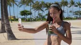 obrázky : Fitness selfie woman drinking green vegetable smoothie taking self portrait photograph with smart phone after running exercise workout on beach. Healthy lifestyle with fit Asian Caucasian girl.