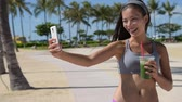 gıda : Selfie fitness woman drinking green vegetable smoothie taking self portrait photograph with smart phone after running exercise workout on beach. Healthy lifestyle with fit Asian Caucasian girl. Stok Video