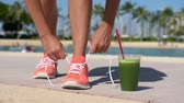 perda de peso : Running woman with green vegetable smoothie. Fitness runner and healthy lifestyle concept with female model tying running shoe laces.