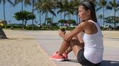 生活方式 : Healthy woman runner drinking green vegetable smoothie resting and relaxing after running. Fitness and healthy lifestyle concept with multicultural Asian Caucasian female model.