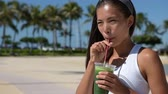 zdraví : Healthy woman drinking green vegetable smoothie for wellness and health. Fitness and healthy lifestyle concept with multicultural Asian Caucasian female model outside in summer. Dostupné videozáznamy