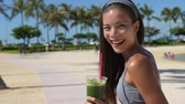 зеленый : Green smoothie vegetable juice - woman drinking vegetable smoothie after fitness running workout on summer day. Fitness and healthy lifestyle concept with beautiful mixed race Asian Caucasian model.