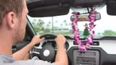 carro : Driver driving car on Hawaii travel with Hula doll dancing on dashboard and lei during road trip. Man driving behind steering wheel.