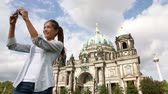 church : Travel woman selfie self portrait  Berlin  Germany. Happy tourist girl in front of Berlin Cathedral  Berliner Dom with Fernsehturm  Berlin TV Tower in the background. Asian Caucasian woman. Stock Footage