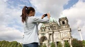 alemão : Travel woman taking photograph in Berlin  Germany. Happy tourist girl in front of Berlin Cathedral  Berliner Dom with Fernsehturm  Berlin TV Tower in the background. Asian Caucasian woman. Vídeos