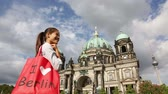 alemão : Tourist in Berlin  Germany on travel visiting landmarks. Woman with shopping bag saying I LOVE BERLIN smiling happy in front Berlin Cathedral  Berliner Dom and Fernsehturm  Berlin TV Tower.