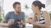 сидящий : Cafe couple looking at smart phone screen app laughing having fun on date drinking coffee in summer. Young man using smartphone talking with Asian woman sitting outdoors. Friends in late 20s.