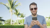 móvel : Smartphone man sms texting using app on smart phone outdoors in summer. Handsome young casual man using mobile cell phone smiling happy wearing sunglasses. Urban male hipster. RED EPIC 90 FPS.