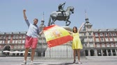 Мадрид : Madrid people showing Spain flag on Plaza Mayor cheerful and happy in Spain. Cheering celebrating young woman and man holding and showing flags to camera on the famous square in front of statue.