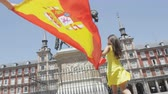pessoas : Madrid, Spain. People with Spanish flag cheering happy celebrating showing flags on Plaza Mayor. Excited young woman and man running over camera on the famous square.