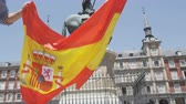 vítěz : Spanish flag. People cheering celebrating showing Spain flag in Madrid on Plaza Mayor. Happy excited young woman and man running with flags towards camera on the famous square. RED EPIC SLOW MOTION.