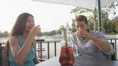 gıda : Couple drinking sangria toasting happy having fun sitting at cafe table outdoors in Madrid, Spain in El Retiro city park. Romantic couple lifestyle in Buen Retiro Park, Parque el Retiro. Stok Video