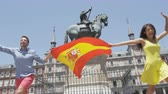 два человека : Spain - Madrid people with Spanish flag cheering happy celebrating showing flags on Plaza Mayor. Excited young woman and man running over camera on the famous square.