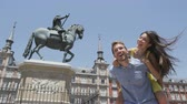 Мадрид : Couple having fun piggyback laughing happy in love in Madrid on Plaza Mayor. Joyful young woman and man on famous square in front of statue. Spain. RED EPIC SLOW MOTION. Стоковые видеозаписи