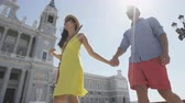 vacation : Couple walking holding hands in Madrid, Spain in front of landmark and tourist attraction Almudena Cathedral.