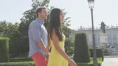 milenec : Couple holding hands walking romantic on city park square in Madrid, Plaza de Oriente, Famous landmark in Madrid, Spain with the Royal Palace in background. RED EPIC SLOW MOTION.