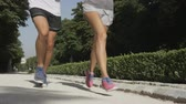 Sport couple running jogging in city park. Runners exercising - woman and man runner training on run living healthy active lifestyle in Retiro Park in Madrid, Spain, Europe. RED EPIC SLOW MOTION. Stok Video