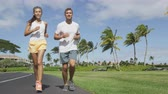 pessoas : Sport couple exercising running outside on street in summer. Happy active young fit adults jogging together with tropical background in city park or resort road. Asian and Caucasian people.