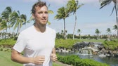 бегать трусцой : Healthy active man runner running in tropical park. Portrait of handsome young male jogger training cardio going for a run in city park or resort with palm trees in the background in summer.