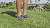 homens : Running shoes footwear in grass in park. Mens shoes outdoors close up. Male sport fitness footwear on man resting before jogging outside. Vídeos