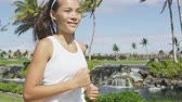 zdraví : Young woman jogging on city street during summer. Asian girl doing cardio exercise training the body to lose weight and staying fit and in shape. Portrait waist up of female jogger going for a run. Dostupné videozáznamy