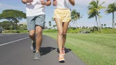 fitness : Running sport couple exercising jogging outside on street in summer. Happy active young fit adults on run together with tropical background in city park or resort road. Young people living healthy.