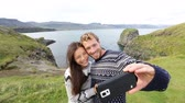 islândia : Tourists on travel taking selfie self portrait photo with smartphone on Iceland. Happy couple sightseeing taking pictures using smart phone visiting Arnarstapi, Snaefellsnes, Iceland.