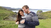 мобильный : Couple on using smartphone app on Iceland. Happy couple using travel apps or map on smart mobile cell phone sightseeing visiting Arnarstapi, Snaefellsnes, Iceland. Стоковые видеозаписи