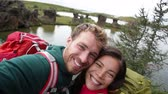 seyahat : Selfie - travel couple on lake Myvatn Iceland. Friends taking selfies photo having fun traveling together visiting Icelandic tourist destination landmarks. Lake Myvatn lava columns, Iceland. Stok Video