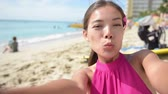 mixed race : Selfie beach travel woman self portrait video on Waikiki beach smiling happy in slow motion blowing a kiss and give wink to camera. Multiracial Caucasian Asian girl in Honolulu, Oahu, Hawaii, USA. Stock Footage